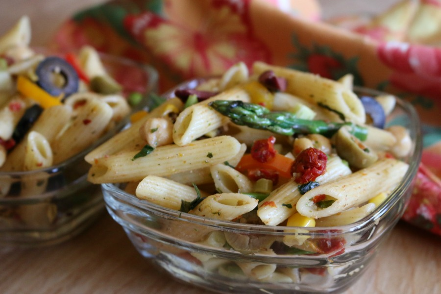 Three Olive Pasta Salad - pasta salad loves vegetables, you can use nearly any type of vegetable in pasta salad. I like using bell pepper, zucchini, asparagus, a little onion. In this recipe I added garbanzo beans and sun dried tomatoes. The sun dried tomatoes really give the salad a nice tangy bite, along with the three variaties, of olives.