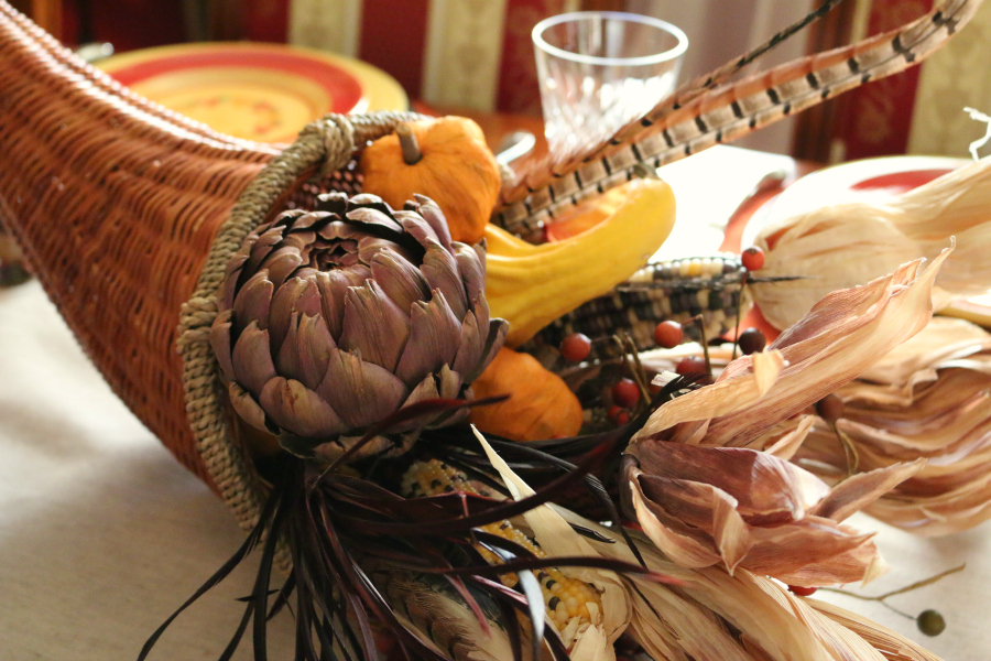 The centerpiece was filled with corn, feathers, pumpkins, dried purple artichoke, and squash.